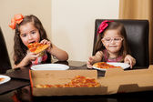 Pretty little Hispanic girls eating pizza together at home — ストック写真