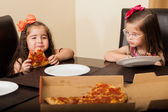 Beautiful siblings having fun and eating some pizza at home — Stockfoto