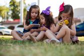 Potrait of three cute little girls each one using their own smart phone at a park — Stock Photo