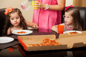 Beautiful little friends having pizza at home while a mother supervises and serves them — Foto Stock