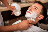 Getting shaved in a barber shop — Stock Photo