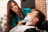 Female barber shaving a man — Stock Photo