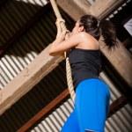Cute girl climbing a rope — Stock Photo