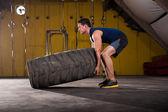 Flipping a tire in a gym — Stock Photo