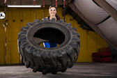 Happy girl flipping a tire — Stock Photo