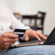 Closeup of a man using his credit card and laptop to buy some stuff online — Stock Photo #47362779