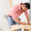 Handsome young carpenter using a tape measure to mark down a wood board dimensions before cutting it — Stock Photo #47362571