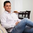 Attractive Hispanic young man relaxing in the living room at home — Stock Photo #47362735