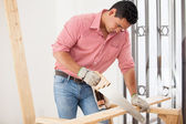 Young Latin contractor doing some carpentry work at a house — Stock Photo