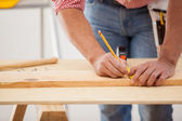 Closeup of a carpenter marking down some dimensions in a wood board — Stock Photo