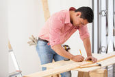 Handsome young carpenter using a tape measure to mark down a wood board dimensions before cutting it — Stock Photo