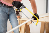 Closeup of a plumber using a hacksaw to cut down some pipes — Stock Photo