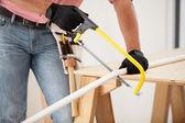 Closeup de um encanador usando uma serra de cortar alguns canos — Fotografia Stock