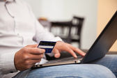 Close de um homem usando seu cartão de crédito e um laptop para comprar algumas coisas na internet — Fotografia Stock