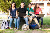 Happy students using technolgy — Stock Photo