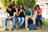 Teens busy with cell phones — Stock Photo