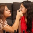 Brunette using an eyelash curler on her friend — Stock Photo #51469127