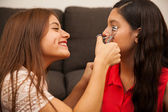 Teenager curling her friend's eyelashes — Stok fotoğraf