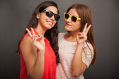 Girlfriends doing a peace sign — Stockfoto