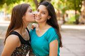Teen kissing her friend in  cheek — Stock Photo