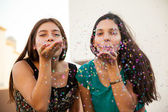 Friends blowing some confetti — Stockfoto