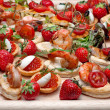Lot of canape with shrimp, caviar, strawberries and other on wo — Stock Photo #13444376