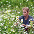 Beautiful young woman sitting on a flowering meadow with daisies — Stock Photo