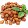 Stock Photo: Heap of fresh shelled hazelnuts with green leaves isolated on wh