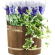 Composition of artificial flowers in old wooden barrel isolated — Stock Photo #25604011