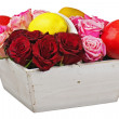 Flower arrangement of red roses and fruits in wooden basket isol — Stock Photo