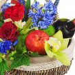 Flower arrangement of roses, orchids, fruits and bottle of wine — Stock Photo #27804151