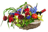 Flower arrangement of roses, orchids, fruits and bottle of wine — Stock Photo