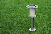 Solar-powered lamp on green grass background. — Stock Photo