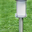 Solar-powered lamp on green grass background. — Stock fotografie
