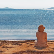 Portrait of young woman on the beach near the sea sitting wearin — Stock Photo