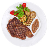 Grilled steaks, baked potatoes and vegetables on white plate on — Stock Photo