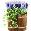 Composition of artificial flowers in old wooden barrel isolated — Stock Photo #35308815