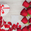 Stock Photo: Valentines Day gift, roses and paper on wooden background.