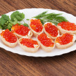 Stock Photo: Tartlets with red caviar on wooden background.