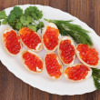 Tartlets with red caviar on wooden background. — Stock Photo