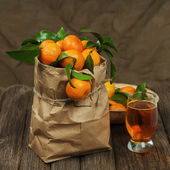 Fresh tangerines in recycle paper bag and glass of juice on wood — Stock Photo