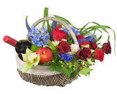 Flower arrangement of roses, orchids, fruits and bottle of wine. — Stock Photo