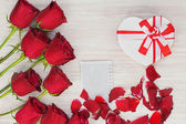 Valentines Day gift, roses and paper on wooden background. — Φωτογραφία Αρχείου