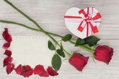 Valentines Day gift, roses and paper on wooden background. — Стоковое фото