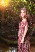 Beautiful girl in floral dress in forest. — Stock Photo