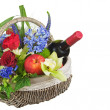 Flower arrangement of roses, orchids, fruits and bottle of wine. — Stock Photo #42771301