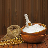 Flour in wooden bowl and wheat in burlap bag. — Stock Photo