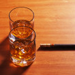 Highball whiskey glass with ice and cigar on wooden background. — ストック写真