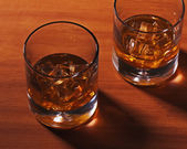 Highball whiskey glass with ice on wooden background. — Stock Photo