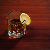 Highball whiskey glass with ice and lemon on wooden background. — Stock Photo